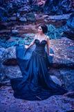 Asien kvinna i svart långt klänninganseende på skog Fotografering för Bildbyråer