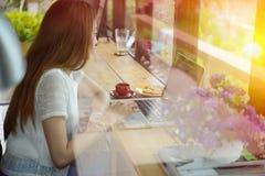 Asien kvinna som använder bärbara datorn i coffee shop Arkivbilder