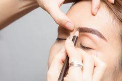 Asien kvinna som applicerar den permanenta sminkögonbryntatueringen arkivfoton