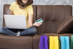 Asien kvinna som direktanslutet hemma shoppar Seaching produkt i shoppingwebsite och lön vid kreditkorten Arkivfoto