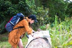 Asien kvinnafotvandrare eller handelsresande med ryggsäckkontrollöversikten som finner riktningar i vildmarkområde, verklig utfor Royaltyfria Foton