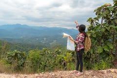 Asien kvinnahandelsresande med ryggsäckkontrollöversikten som finner riktningar i vildmarkområde, utforskare Royaltyfri Bild