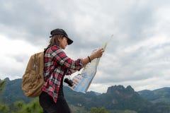 Asien kvinnahandelsresande med ryggsäckkontrollöversikten som finner riktningar i vildmarkområde, utforskare Royaltyfri Foto