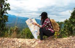Asien kvinnahandelsresande med ryggsäckkontrollöversikten som finner riktningar i vildmarkområde, utforskare Arkivbilder