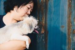 Asien kvinnor och lyckligt krama för hund med behållaren Royaltyfri Foto