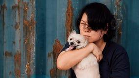 Asien kvinnor och lyckligt krama för hund med behållaren Royaltyfri Bild