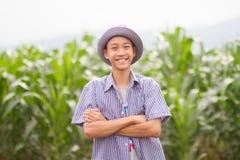 Asien-Landwirtstellung auf den mittleren Maisgebieten und lächelndem Gesicht stockbild