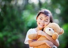 Asien liten flicka med dockabjörnen royaltyfri fotografi