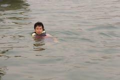 Asien man i flytvästar som simmar i floden Arkivbild