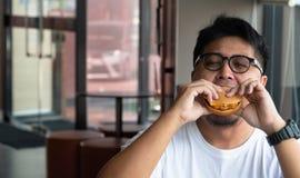 Asien-Mann isst Hamburger in einem Schnellrestaurant und genie?t k?stliche Nahrung Mann in einem weißen T-Shirt und in Gläsern, d stockfotos