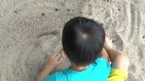 Asien-melayu malaysischer Junge, der Sand an einem Strand spielt stock video