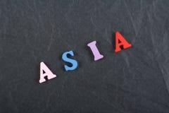 ASIEN ord på svart brädebakgrund som komponeras från träbokstäver för färgrikt abc-alfabetkvarter, kopieringsutrymme för annonste Royaltyfria Foton