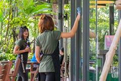 Asien personalkvinnor som förbi gör ren wipen per exponeringsglas Arkivfoto