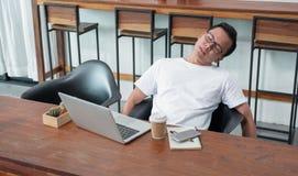 Asien sitter den tillfälliga mannen tillbaka känseln som tröttas från arbete på bärbara datorn i coffe royaltyfria bilder
