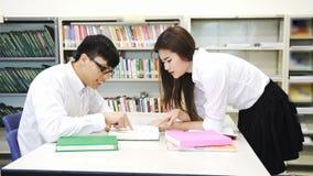 Asien-Studenten, die in der Bibliothek arbeiten und unterrichten stock footage