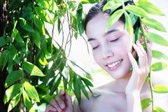 Asien vänder mot kvinnan med ny vård- hud som poserar på naturen Royaltyfria Bilder