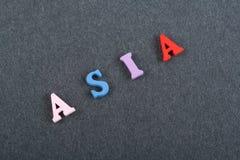 ASIEN-Wort auf dem schwarzen Bretthintergrund verfasst von den hölzernen Buchstaben des bunten ABC-Alphabetblockes, Kopienraum fü Stockfotografie