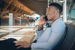 Asientan al hombre de negocios joven en el aeropuerto que sonríe y que habla b foto de archivo libre de regalías