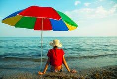 Asiento adolescente de la muchacha en una playa Fotografía de archivo