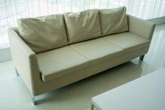 Asiento beige del sofá de la cubierta del cuero del color en piso limpio foto de archivo libre de regalías