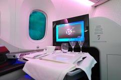 Asiento cómodo de la clase de negocios con la cena del ajuste Qatar Airways a bordo Boeing 787-8 Dreamliner en Singapur Airshow Imagen de archivo
