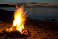 Asiento cerca de la hoguera romántica en la puesta del sol de observación de la playa Fotografía de archivo libre de regalías