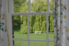 Asiento de jardín visto a través de ventana fotos de archivo libres de regalías
