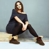Asiento de la muchacha de la moda, presentando contra gris Imagen de archivo