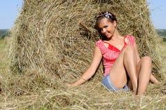 Asiento de la mujer joven cerca del haystack Fotografía de archivo