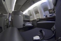 Asiento de la primera clase en Boeing 777-300 en un aeroplano comercial Imagenes de archivo