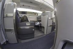 Asiento de la primera clase en Boeing 777-300 en un aeroplano comercial Imágenes de archivo libres de regalías