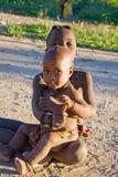 Asiento de los niños de Himba en la arena Imágenes de archivo libres de regalías