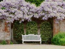 Asiento de madera blanco adornado en el ajuste floral Imagen de archivo