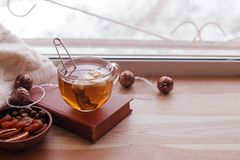 Asiento de ventana caliente y acogedor con la taza de té y la pila de libros y de guirnalda en el travesaño de madera de la venta foto de archivo libre de regalías