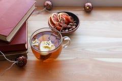 Asiento de ventana caliente y acogedor con la taza de té y la pila de libros y de guirnalda en el travesaño de madera de la venta imágenes de archivo libres de regalías