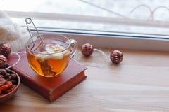 Asiento de ventana caliente y acogedor con la taza de t? y la pila de libros y de guirnalda en el travesa?o de madera de la venta imagenes de archivo