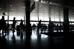 Asiento de ventana grande que descansa a los pasajeros blancos negros del sol de la silueta que esperan el aeropuerto del termina foto de archivo
