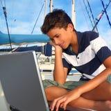 Asiento del adolescente del muchacho en el ordenador portátil del puerto deportivo del barco Fotos de archivo libres de regalías