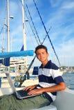 Asiento del adolescente del muchacho en el ordenador portátil del puerto deportivo del barco Imagenes de archivo