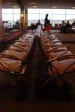 Asiento del aeropuerto con las hojas de ruta (traveler) en fondo Imágenes de archivo libres de regalías