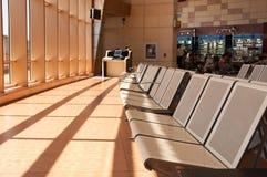 Asiento en la puerta de un término de la salida del aeropuerto internacional Foto de archivo