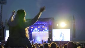 Asiento femenino de la fan en los hombros y las manos que agitan en concierto, muchedumbre de baile iluminada por la luz colorida almacen de metraje de vídeo