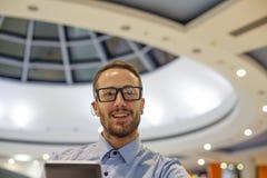 Asiento joven del hombre de negocios en la tabla en el restoran y el uso de móvil Imagen de archivo libre de regalías