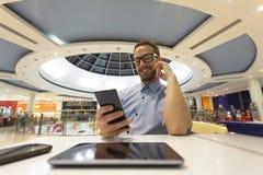 Asiento joven del hombre de negocios en la tabla en el restoran y el uso de móvil Fotos de archivo libres de regalías
