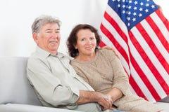 Asiento mayor feliz de los pares delante de la bandera americana Foto de archivo libre de regalías