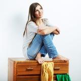 Asiento modelo joven en el armario para la ropa. Fotografía de archivo