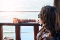 Asiento que se sienta de la mujer joven en el barco mientras que agua potable que ve el sc Fotos de archivo