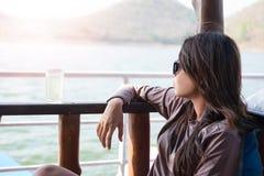 Asiento que se sienta de la mujer joven en el barco mientras que agua potable que ve el sc Imágenes de archivo libres de regalías