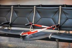 Asiento quebrado defectuoso asegurado con una cinta plástica roja y blanca de la barrera en la zona de espera de un aeropuerto foto de archivo
