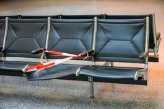 Asiento quebrado defectuoso asegurado con una cinta plástica roja y blanca de la barrera en la zona de espera de un aeropuerto fotografía de archivo